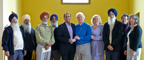 Photogrpah of the presentation, by Paul Uppal MP, of a cheque for £5000 to Revd Donald Ryan for the development of the atrium